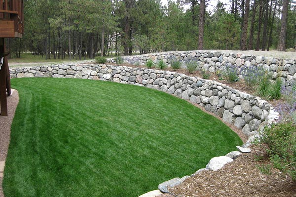 Beautiful backyard retaining walls with grey boulders in Black Forest.