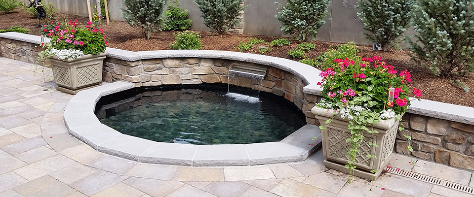 Small pool with waterfall as water feature on patio.