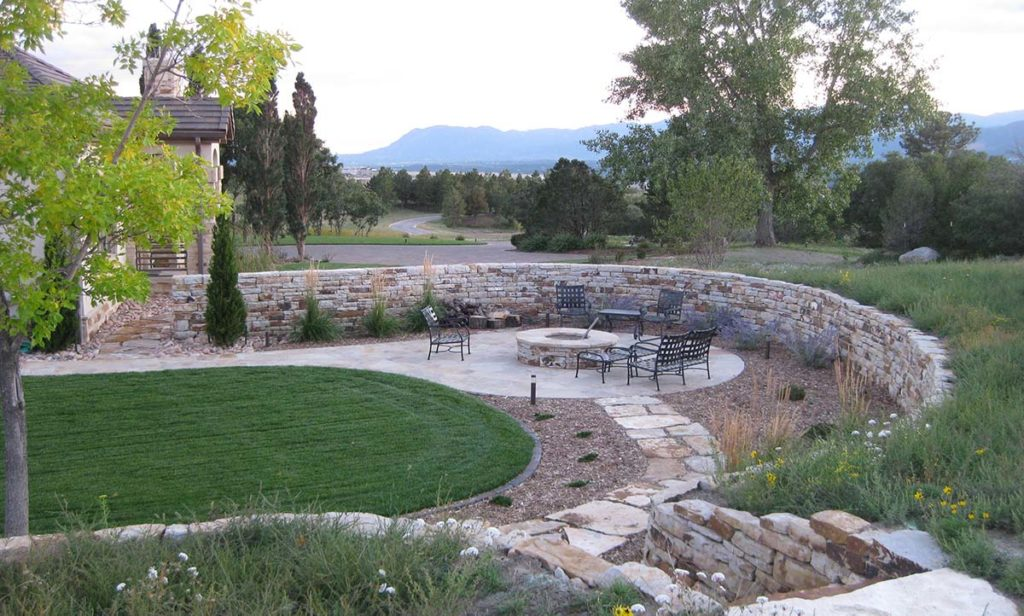 Outdoor living space with fire pit and retaining wall.