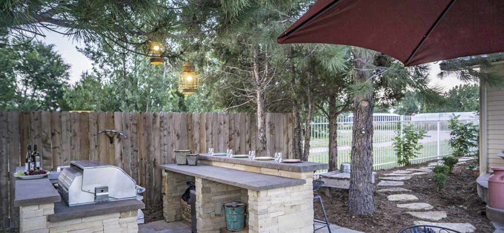 This outdoor kitchen is lit up with two standard 120v light fixtures hanging from the pine trees.
